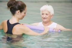 Terapeuta y paciente mayor en piscina hidráulica Fotos de archivo libres de regalías