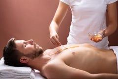 TerapeutApplying Wax On mans br?stkorg fotografering för bildbyråer