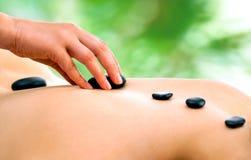 Terapeuthand som gör varm stenmassage royaltyfri bild