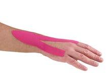 Terapeutisk behandling av handleden med kinesiotexbandet. Arkivbild