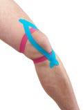 Terapeutisk behandling av knäet med kinesiotexbandet. Arkivfoto