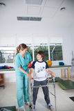 Terapeutkvinna med pojken i rehab royaltyfri foto