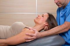 Terapia d'allungamento cervicale con il terapista nel collo della donna Fotografia Stock