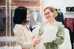 Terapia da compra na ação Duas mulheres bonitas com os sacos de compras que olham se com sorriso ao andar no imagens de stock