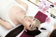 Terapia del balneario para la mujer joven que recibe la máscara facial en el salo de la belleza Imagenes de archivo