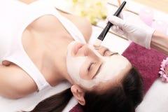 Terapia del balneario para la mujer joven que recibe la máscara facial en el salo de la belleza Fotos de archivo libres de regalías