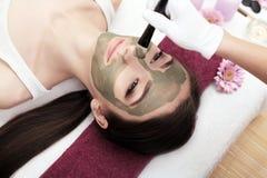 Terapia del balneario para la mujer joven que recibe la máscara facial en el salo de la belleza Imagen de archivo libre de regalías