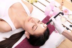 Terapia del balneario para la mujer joven que recibe la máscara facial en el salo de la belleza Imagen de archivo