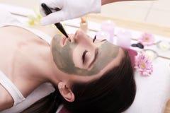 Terapia del balneario para la mujer joven que recibe la máscara facial en el salo de la belleza Imágenes de archivo libres de regalías