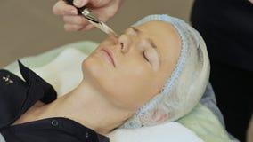 Terapia del balneario para la mujer joven que tiene máscara cosmética en el salón de belleza Aplicación de una máscara del chocol almacen de video