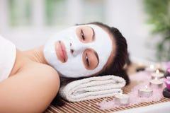 Terapia del balneario para la mujer joven que tiene máscara facial en el salón de belleza Fotos de archivo