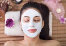 Terapia del balneario para la mujer joven que tiene máscara facial en el salón de belleza Imagenes de archivo