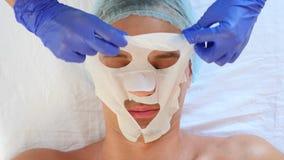 Terapia del balneario para los hombres hermosos que reciben la máscara facial 4K Cámara lenta Recepción de un cosmetologist almacen de metraje de vídeo