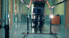Terapia di recupero ad una clinica Il paziente prova a muovere le gambe, indossanti la protesi speciale archivi video