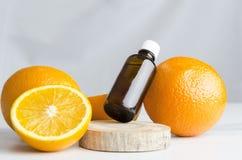 Terapia do aroma no salão de beleza dos termas Laranjas e óleo alaranjado para cuidados médicos na placa de madeira, tabela de má fotos de stock