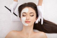 Terapia dos termas para a jovem mulher que tem a máscara facial no salão de beleza - imagens de stock