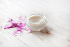 Terapia facial poner crema cosmética del tratamiento médico del skincare de la piel cansada crema de cara con los pétalos color d Fotografía de archivo