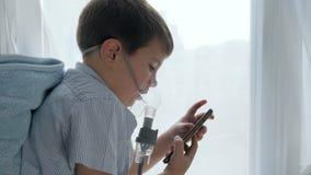 Terapia medica se difficoltà che respira, bambino nella maschera dall'nebulizzatori con lo smartphone nelle mani stock footage