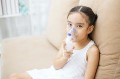 Terapia paciente da inalação da criança asiática bonito pela máscara de inhal imagens de stock