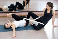 Terapia practicante femenina de la yoga de dos yoguis en clase imagen de archivo
