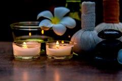 Terapia tailandesa del aroma de los tratamientos de la composición del balneario con las velas y las flores del Plumeria en cierr Foto de archivo