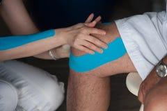 Terapiband för ett öm knä arkivbild