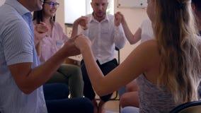 Terapii sesja, grupa szczęśliwi ludzie podnosi ręki wpólnie, obniża i wtedy oklaskuje each innego obsiadanie w okręgu zbiory wideo