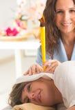 Terapist, das eine Ohrkerzentherapie tut lizenzfreie stockfotos