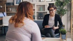 Terapista allegro che discute disordine alimentare con il paziente obeso durante la sessione archivi video