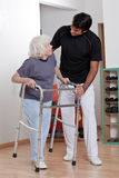 Terapista che aiuta il camminatore paziente di uso Immagini Stock Libere da Diritti