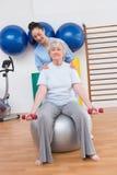 Terapista che aiuta le teste di legno adatte della donna senior sulla palla di esercizio Fotografia Stock Libera da Diritti