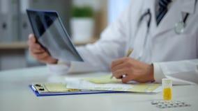 Terapista che analizza i raggi x pazienti dei polmoni per annotare diagnosi, trattamento fotografia stock libera da diritti