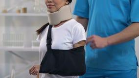 Terapista che applica paziente femminile sorridente in imbracatura cervicale del braccio del collare della schiuma stock footage