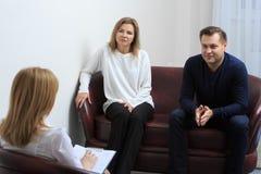 Terapista che ascolta i suoi pazienti e che prende le note fotografia stock