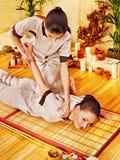 Terapista che dà allungando massaggio alla donna. Fotografia Stock