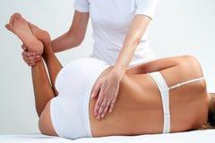 Terapista che fa massaggio più lombo-sacrale sulla donna Fotografia Stock