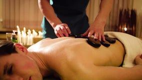 Terapista che fa terapia di pietra cinese ad un uomo video d archivio
