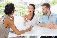 Terapista che parla con le coppie che si siedono allo scrittorio Fotografie Stock Libere da Diritti