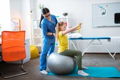 Terapista dai capelli lunghi concentrato in uniforme blu che corregge posizione fotografie stock