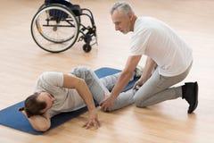 Terapista fisico uscente che allunga il paziente disabile nella palestra Fotografie Stock Libere da Diritti