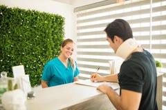 Terapista Looking At Athlete che riempie forma medica alla ricezione C fotografia stock libera da diritti