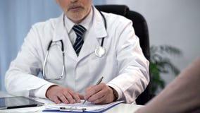 Terapista maschio che compila modulo di iscrizione e che consulta paziente, appuntamento fotografia stock libera da diritti