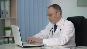 Terapista stanco che riempie negli archivi record elettronici dopo l'esame paziente video d archivio