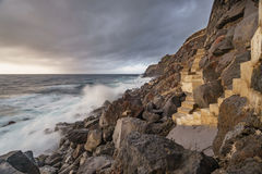 Terceira island coastline with stairs and waves breaking, long exposure. Cloudy sunset and coastline with high cliffs and long exposure of waves breaking over Stock Image