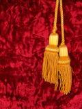 Terciopelo rojo con dos borlas de oro Imagenes de archivo