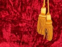 Terciopelo rojo con las borlas amarillas Imagen de archivo libre de regalías