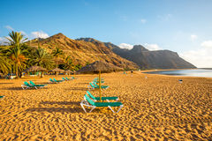 Teresitas beach near Santa Cruz de Tenerife. Teresitas beach with sunbeds and mountains on the background on the sunset on Tenerife island, Spain Royalty Free Stock Photos