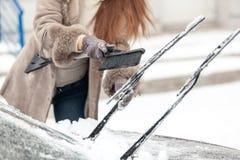 Tergicristalli dell'automobile di pulizia della donna da neve con la spazzola Fotografia Stock