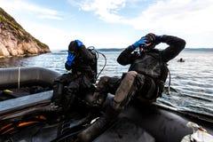 Teriberka, Russia - 29 luglio 2017: Due subaquei che si tuffano da una barca nell'acqua Colpo in mare di Barents immagine stock