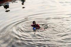 Teriberka, Russie - 27 juillet 2017 : Plongeur autonome flottant sur la surface de la mer près du bateau photos stock